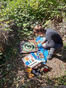 Woman painting a snake on a hibernacula